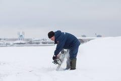 喀山,俄罗斯- 2017年1月19日:俄国人MoE救生员切开与锯的冰-救助者冬日durin的 免版税库存照片