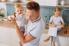 喂养他的孩子的严肃的聪明的人 免版税图库摄影