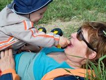喂养他的母亲的男孩 免版税库存照片