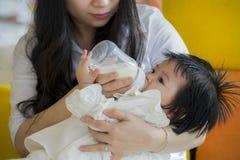 喂养她有惯例瓶的年轻愉快和甜亚裔日本妇女生活方式坦率的画象美丽的女婴在 免版税库存图片