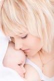 喂养她的亲吻母亲的婴孩乳房 免版税图库摄影