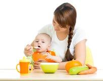 喂养她的女婴的新母亲匙子在服务台 图库摄影