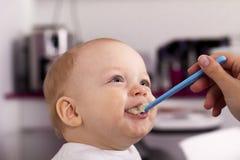 喂养她的小可爱的儿子的母亲 逗人喜爱男婴吃 免版税库存图片
