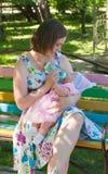 喂养她的母亲的婴孩 图库摄影