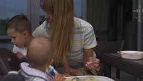 喂养她的男婴儿子的年轻母亲坐在儿童位子-家庭价值观温暖的颜色夏天场面 股票录像