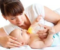 喂养她的婴孩的新母亲 图库摄影