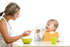 喂养她逗人喜爱的婴孩的新母亲匙子 免版税库存图片
