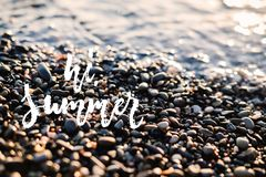 喂,夏天-在海滩海或海洋背景的手拉的正面假日词组上写字 乐趣刷子墨水行情为 免版税图库摄影