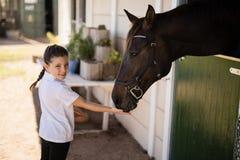 喂养一匹马的女孩在槽枥 免版税库存照片
