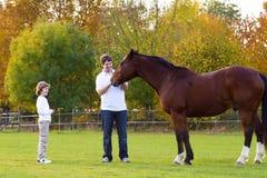 喂养一匹马的父亲和儿子在一秋天天 图库摄影