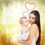 喂养她可爱的婴孩的愉快的母亲 免版税库存照片