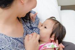 喂养她的母亲的乳房女儿 免版税库存图片