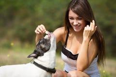 喂养她的牛头犬的青少年的女孩 图库摄影