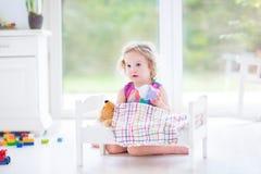 喂养她的玩具熊的滑稽的小孩女孩在晴朗的屋子里 库存照片