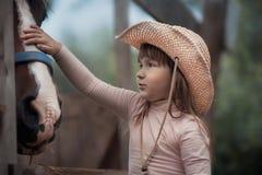 喂养她的马的女孩 库存照片