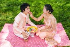 喂养她逗人喜爱的新郎的亚裔泰国新娘 免版税库存图片