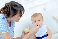 喂养小女儿的母亲 免版税库存图片