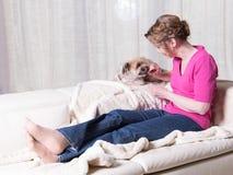 喂养小狗的紫色的可爱的妇女 免版税库存图片