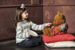 喂养玩具熊的女孩 免版税库存照片