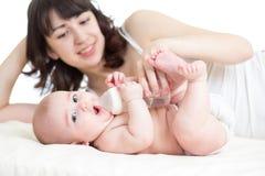 喂养从瓶她的婴孩的母亲 免版税库存照片