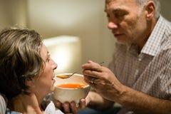 喂养他病的妻子的有同情心的老人 免版税库存图片