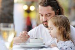 喂养他的小女孩的父亲 免版税库存图片