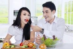 喂养他的妻子用沙拉的人 免版税库存图片