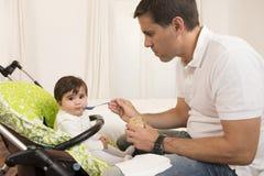 喂养逗人喜爱的可爱的女婴的父亲 免版税库存图片