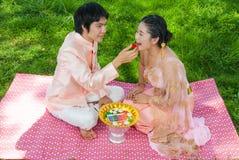 喂养他逗人喜爱的新娘的亚裔泰国新郎 免版税库存图片