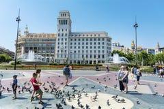 喂养鸽子在卡塔龙尼亚广场,巴塞罗那,西班牙的游人 免版税库存照片