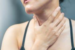 喉咙痛痛苦妇女 与感到的喉咙痛的妇女手感人的脖子坏 医疗保健和医学概念 库存照片