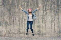 喜悦和自由,生活的概念不出问题 牛仔裤衣裳的疯狂,极端愉快的女孩和桃红色帽子尖叫和jumpin 免版税库存照片