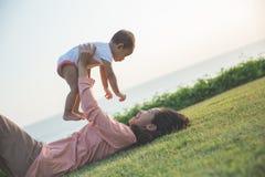 喜悦妈妈和婴孩在公园 库存照片