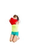 喜悦拿着红色心脏的爱跳跃的青少年的女孩 免版税图库摄影