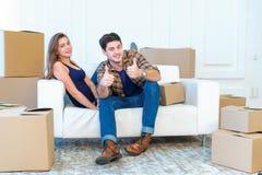 喜悦搬入房子 拿着箱子的一对爱恋的夫妇  免版税库存图片