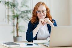 喜悦的快乐的红色haird女性经济学家在办公室内部在企业球形开发财政起始的项目,摆在,工作 库存照片