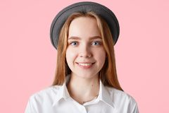 喜悦的愉快的十几岁的女孩射击的关闭为普遍的时装杂志摆在,戴时髦帽子,并且典雅的白色衬衣,有绅士 免版税库存照片