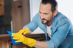 喜悦的男性擦净剂与清洁布一起使用 免版税库存照片