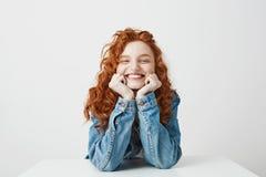 喜悦的红头发人女孩微笑的欣喜用在坐在白色背景的桌上的面颊的手 库存照片