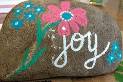 喜悦-与桃红色和蓝色花的被绘的岩石 免版税库存图片