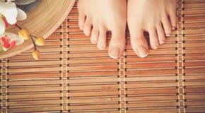 喜欢在地板上的美好的妇女腿 在白人妇女的背景美好的查出的行程 免版税库存照片