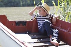 他喜欢坐在河的一条小船并且看  库存图片