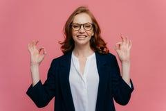 喜欢的女性金融家做好姿态用两只手,有在面孔的宜人的微笑,佩带礼服,有正面微笑, 免版税图库摄影
