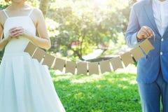 喜爱婚姻夫妇,婚姻花束在新娘和新郎的手上 免版税库存照片