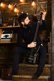 喜爱的活动 人有胡子的音乐家喜欢与低音吉他,木背景 有胡子的人举行黑色 免版税库存图片
