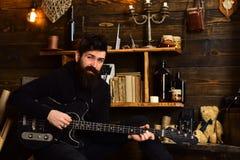 喜爱的活动 人有胡子的音乐家喜欢与低音吉他,木背景 舒适温暖的大气的人 免版税库存照片