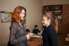 喜爱的老师 微笑对她的老师的美丽的逗人喜爱的小女孩在教训学校课程创造性学习期间 库存照片