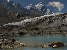 喜马拉雅冰川的巨大的高山的脚的一个小蓝色湖与白色冰的在它的峰顶,一个旅游夏天 免版税图库摄影