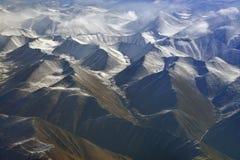 喜马拉雅山的山脉,拍摄与了不起的高度:棕色用白色雪报道的峡谷、峰顶和云彩 免版税库存照片