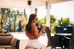 喝一个五颜六色的鸡尾酒的美丽的少妇佩带的泳装坐海滩俱乐部酒吧的客舱 震惊 免版税库存照片